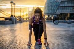 Спортсменка готовая для того чтобы сделать ее разминку раннего утра в городе стоковая фотография