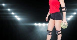 Спортсменка держа гандбол против светов потока в предпосылке Стоковые Фото