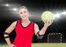 Спортсменка держа гандбол против стадиона в предпосылке Стоковая Фотография RF