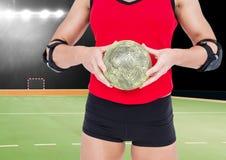 Спортсменка держа гандбол против стадиона в предпосылке Стоковое Фото