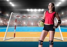 Спортсменка держа гандбол против стадиона в предпосылке Стоковые Фото