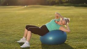 Спортсменка делая подбрюшные хрусты на шарике пригонки сток-видео