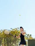 Спортсменка играя теннис на суде Стоковые Изображения