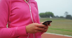 Спортсменка используя мобильный телефон на месте спорт 4k видеоматериал
