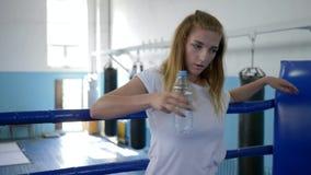 Спортсменка отдыхая после трудных разминки и питьевой воды от бутылки стоя на боксерском ринге в спортзале акции видеоматериалы
