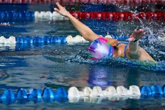 Спортсменка плавает со стилем бабочки Брызгает scatter воды в различных направлениях стоковые фотографии rf