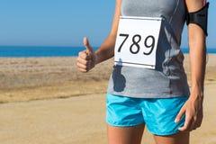 Спортсменка при номер старта гонки делая большие пальцы руки вверх стоковые фотографии rf