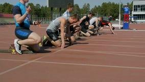 Спортсмены молодых человеков начинают к спринту 100 метров в стадионе акции видеоматериалы