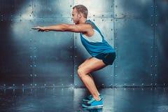 спортсмены подходящий мужской человек тренера делая сидения на корточках, силу прочности разминки фитнеса crossfit концепции Стоковая Фотография RF