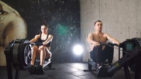 Спортсмены разрабатывая на машине rowing сток-видео