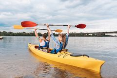 Спортсмены сидя в желтом каное чувствуя счастливый выигрывающ приз стоковое изображение rf