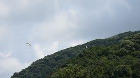 Спортсмены скача от горы с парапланеризмом