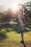 Спортсмен бегуна протягивая ноги outdoors в парке Стоковые Фотографии RF
