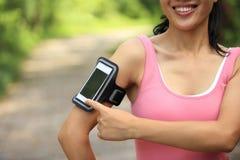 Спортсмен бегуна слушая к музыке в наушниках от умного mp3 плэйер телефона Стоковые Фото