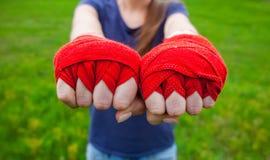 Спортсмен, боксер стоя в парке и простирания девушки обе руки обхваченной в кулаки обернули спорт, красные повязки кладя в коробк Стоковое фото RF