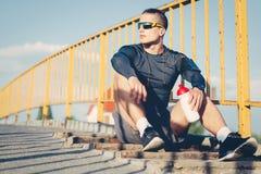 Спортсмен выпивая от пластичной бутылки воды после разминки outdoors Стоковые Фотографии RF
