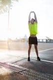 Спортсмен выполняет подогрев путем поднимать ваши руки вверх пока слушающ к музыке в наушниках Стоковые Фотографии RF