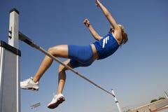 Спортсмен выполняя высокий прыжок Стоковые Фото