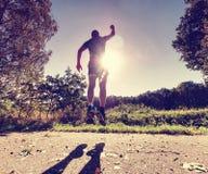 Спортсмен в пределах тренировки в парке Человек бежит или скачет стоковые фото