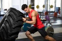 Спортсмен в sportswear нажимая огромное колесо, изолированное на расплывчатой предпосылке спортзала стоковая фотография rf
