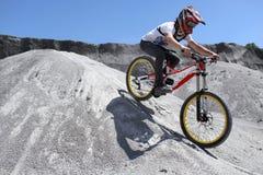 Спортсмен в sportswear на горном велосипеде едет на камнях Стоковые Фото