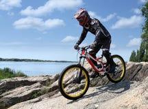 Спортсмен в sportswear на горном велосипеде едет на камнях стоковые изображения rf