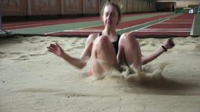 Спортсмен девушки выполняя большой скачок в ящик с песком сток-видео