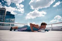 Спортсмен делает нажим-поднимает на солнечной террасе стоковая фотография rf