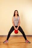 Спортсмен девушки сидит на корточках с весами Стоковое Изображение