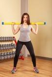 Спортсмен девушки сидит на корточках с fitbar Стоковое Фото