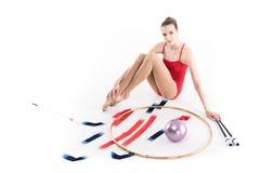 Спортсмен девушки сидя около прибора звукомерной гимнастики и смотря камеру Стоковое Фото