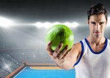 Спортсмен держа гандбол против стадиона в предпосылке Стоковые Изображения