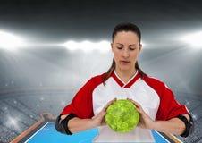 Спортсмен держа гандбол против стадиона в предпосылке Стоковое Изображение RF