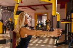 Спортсмен женщины приниматься спортзал на тренере руки Концепция спорта стоковое фото