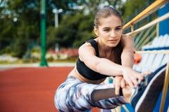 Спортсмен женщины протягивая ноги и разрабатывая на стадионе Стоковые Изображения RF