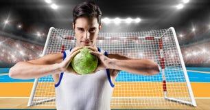 Спортсмен играя гандбол против стадиона в предпосылке Стоковая Фотография RF