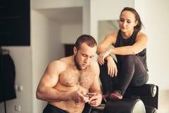 Спортсмен используя отслежыватель фитнеса app мобильного телефона для отслеживая прогресса потери веса Стоковая Фотография RF