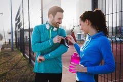 Спортсмен используя телефон для того чтобы слушать к музыке пока бежать и joggi Стоковые Фото