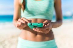 Спортсмен используя разминку пляжа smartphone app фитнеса стоковая фотография rf