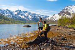 Спортсмен и женщина около озера горы Стоковая Фотография