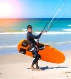 Спортсмен идя к тренировке змея занимаясь серфингом Стоковые Изображения RF