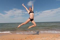 Спортсмен маленькой девочки в купальнике на море скача на пляж стоковое фото