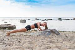 Спортсмен маленькой девочки играя спорт на пляже i Стоковые Фото
