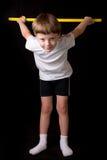 Спортсмен мальчика выполняет тренировки с гимнастической ручкой в спортзале Стоковые Фото