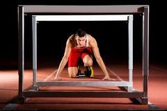 Спортсмен на начиная блоках с барьерами стоковое фото