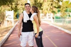 Спортсмен получая поцелуй от его подруги Стоковое Изображение
