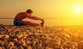 Спортсмен практикуя, йога на пляже на заходе солнца Стоковые Изображения RF