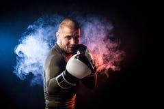 Спортсмен представляя против дыма стоковые изображения
