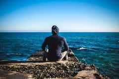 Спортсмен принимая пролом сидя на утесах с горизонтом моря Стоковое фото RF