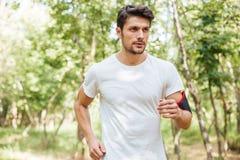 Спортсмен при handband бежать в лесе в утре Стоковая Фотография RF